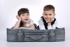 Little boy and girl lying on suitcase Stock Image