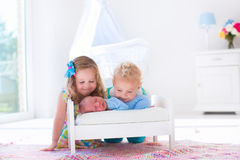 Little boy and girl meet new sibling. Cute little boy and girl kissing newborn brother. Toddler kids meet new born sibling at home. Infant sleeping in toy bed in Stock Image