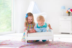 Little boy and girl meet new sibling. Cute little boy and girl kissing newborn brother. Toddler kids meet new born sibling at home. Infant sleeping in toy bed in Stock Images