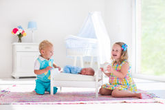 Little boy and girl meet new sibling. Cute little boy and girl kissing newborn brother. Toddler kids meet new born sibling at home. Infant sleeping in toy bed in Royalty Free Stock Image
