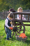 Little boy and girl near wooden cart stock images