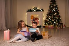 The little boy and girl open Christmas presents Christmas tree new year`s Eve family celebration stock image