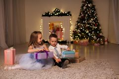 The little boy and girl open Christmas presents Christmas tree new year`s Eve family celebration stock photos