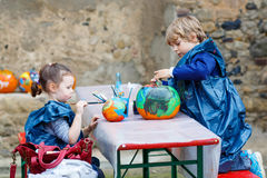 Little boy and girl painting with colors on pumpkin Stock Photos
