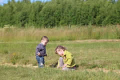 Little boy and girl paly on grass at green meadow Stock Photos