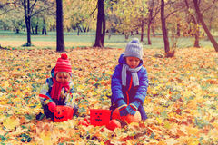 Little boy and girl play with autumn leaves in nature Stock Photo
