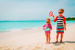 Little boy and girl play beach tennis on vacation. Little boy and girl play beach tennis on sea vacation stock photo