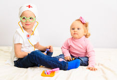 Little boy and girl play doctor indoors Stock Photos
