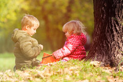 Little boy and girl play with leaves in autumn Stock Image