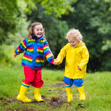 Kids play in rain and puddle in autumn Stock Photography