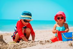 Little boy and girl play with sand on beach stock photography