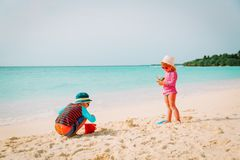 Little boy and girl play with sand on beach. Little boy and girl play with sand on tropical beach Royalty Free Stock Photo