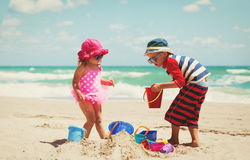Little boy and girl play with sand on beach Stock Photo