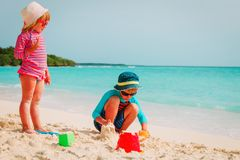 Little boy and girl play with sand on tropical beach. Family vacation Stock Photo
