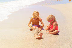 Little boy and girl play with water on beach Royalty Free Stock Images