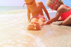 Little boy and girl play with water on beach Royalty Free Stock Photos