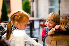 Little boy and girl playing. Little boy ant girl playing on table with toy cars Royalty Free Stock Images