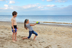 Little boy and girl playing on beach sand. Happy kids playing on beach, with seascape in the background Royalty Free Stock Photos