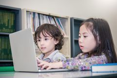 Little boy and girl playing computer games. Small boy and girl tying with laptop. In the library. Education home school concept stock image