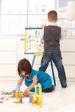Little boy and girl playing at drawing board. Little boy and girl playing together at home with drawing board and toy blocks Royalty Free Stock Photography