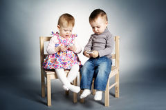 Little boy and girl playing with mobile phones Royalty Free Stock Images