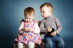 Little boy and girl playing with mobile phones Royalty Free Stock Image