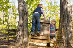 Little boy and girl playing on an old gate Stock Photography
