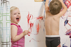 Little boy and girl playing painting on walls  in bathroom, having fun, lifestyle active childhood Royalty Free Stock Photography