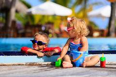 Little boy and girl playing in swimming pool Stock Photos