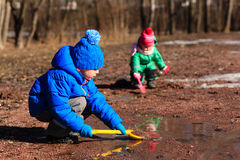 Little boy and girl playing with water in spring Stock Photos