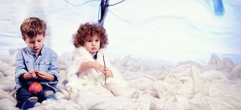 Little boy and girl plays in studio snow forest background Royalty Free Stock Images