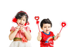 Little boy & girl posing with love symbol. In a white background Royalty Free Stock Images