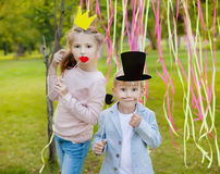 Little boy and girl posing with paper masks on a cheerful children's holiday. Stock Photo