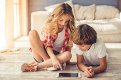 Little boy and girl. Pretty little girl and boy are using a digital tablet and smiling while sitting on the floor at home Stock Images