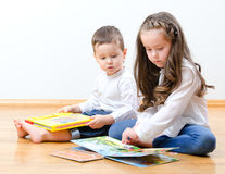 Little boy and girl reading a book. Little boy and girl sitting on the floor and reading a book Royalty Free Stock Photos