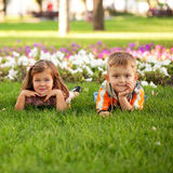 Little boy and girl relaxing on the grass Stock Images