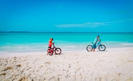 Little boy and girl ride bike on beach. Little boy and girl ride bike on tropical beach royalty free stock photography