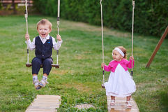Little boy and girl ride in the park on a swing Stock Photo
