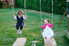Little boy and girl ride on a swing at the playground in the park Royalty Free Stock Photography