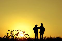 Little boy and girl riding bikes at sunset, active kids sport, A. Sian kid,Silhouette a kid at the sunset, Happy time.family , all living together, is having the stock images