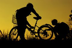 Little boy and girl riding bikes at sunset, active kids sport, Asian kid,Silhouette a kid at the sunset, Happy time. Royalty Free Stock Photo