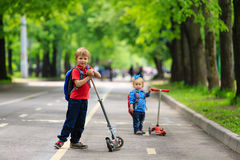 Little boy and girl riding scooters in the city Stock Photography