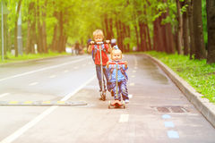 Little boy and girl riding scooters in the city Royalty Free Stock Photo