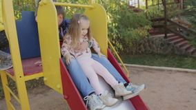 Little boy and girl roll down from the slide stock footage