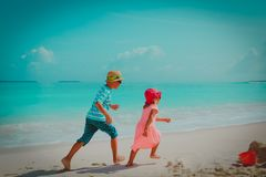 Little boy and girl run play on beach stock photos