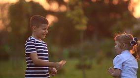 Little boy and girl run and play. They blow dandelion. Sunset stock video footage