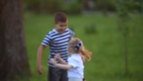 Little boy and girl run and play. They blow dandelion. Sunset stock footage