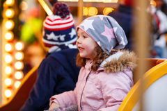 Little boy and girl, siblings on carousel at Christmas market Royalty Free Stock Images
