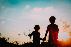 Little boy and girl silhouettes holding hands at sunset. Nature royalty free stock image