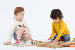 Little boy and girl sit on floor and build railway. From wooden parts on white background Stock Images